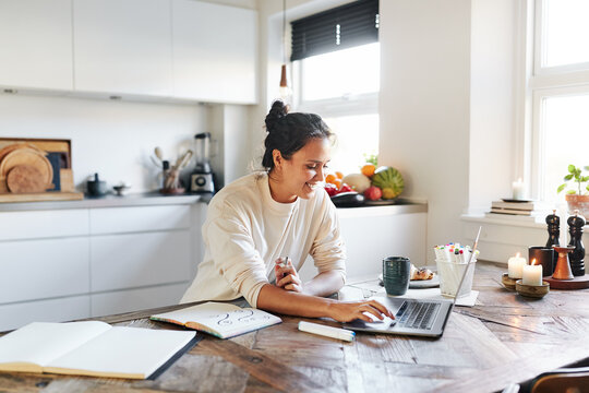 Woman working online at her kitchen table
