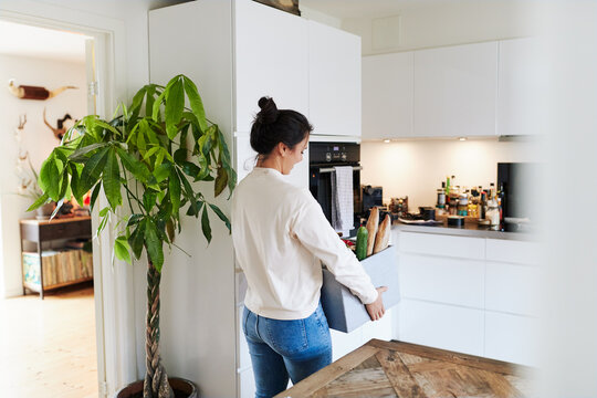 Woman carrying groceries in her kitchen