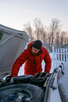 Focused guy repairing car with open bonnet in winter countryside