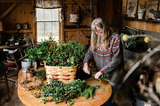 florist making holiday wreath with evergreen and holly