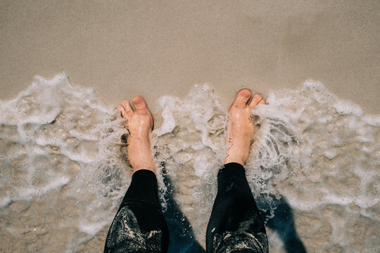 Looking down at feet getting wet by a wave on a sandy beach
