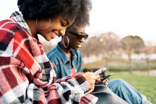 Happy Black Friends Using Phone