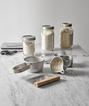 Baking tools and jars of different flour on a marble counter top.