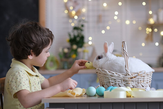 Happy easter. Child boy in bunny ears plays with decorated eggs and hare sits in a wicker basket on the kitchen table. soft focus