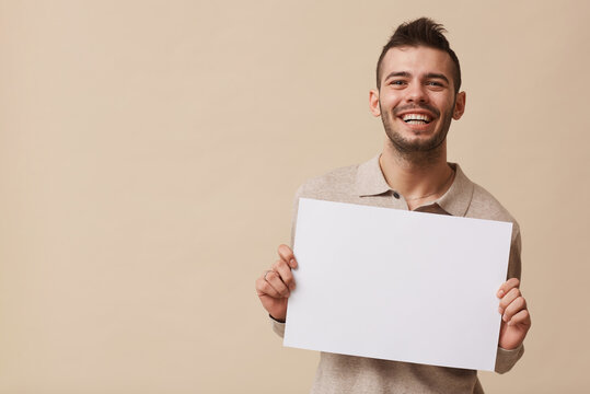 Minimal waist up portrait of carefree young man holding blank white sign and smiling at camera while posing against beige background in studio, copy space