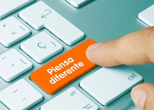 Piensa diferente - Inscripción en la tecla del teclado naranja.