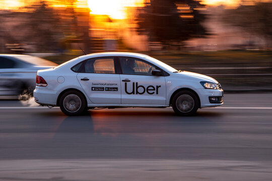 Ukraine, Kyiv - 11 March 2021: White Taxi Uber car moving on the street;