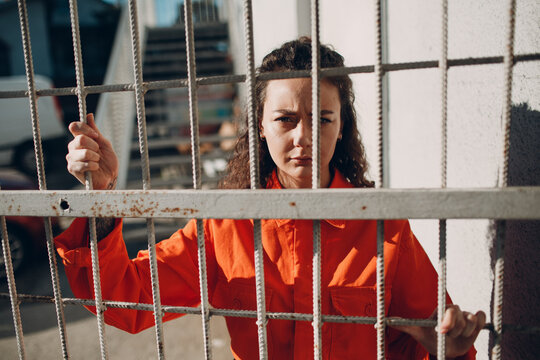 Young woman in orange suit behind jail bars. Female in colorful overalls portrait. Law and justice concept.