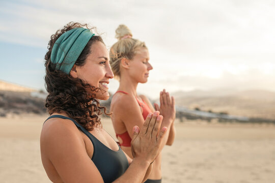 Two sportive women meditating and doing yoga at the beach