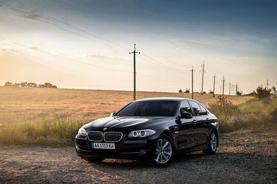 Kherson, Ukraine - June 2019. BMW 5-series F10 in a black color in the field.