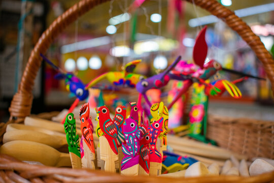 Colorful handmade hummingbird figures hanging inside a basket