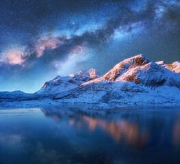 Milky Way above frozen sea coast and snow covered mountains in winter at night in Lofoten Islands, Norway. Arctic landscape with blue starry sky reflected in water, snowy rocks, milky way. Space