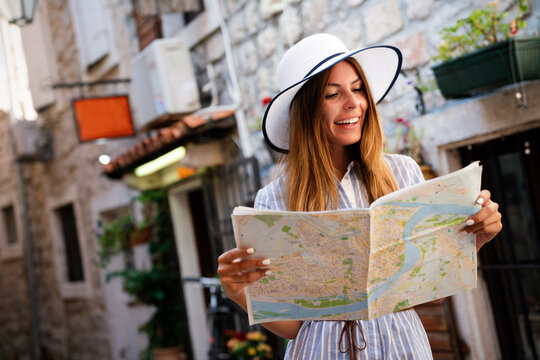 Happy young woman with map in city. Travel tourist people fun concept.