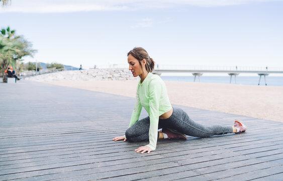 Slim woman practicing yoga on quay