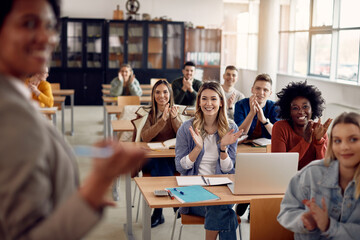 Happy university students applauding to their teacher during lecture in the classroom.