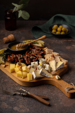 Cheese platter with different cheeses, dried tomatoes, nuts, honey and dates on rustic wooden background. Retro styled cheese variety selection on wood board. Selective focus. High quality photo