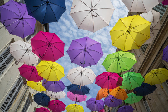 Art installation with colourful umbrellas in a street in Arles, Provence, France