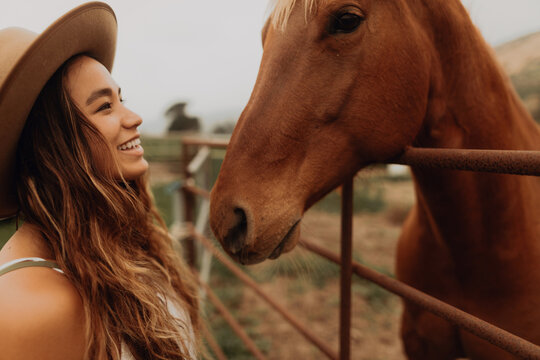 Young woman in felt hat face to face with horse, Jalama, California, USA