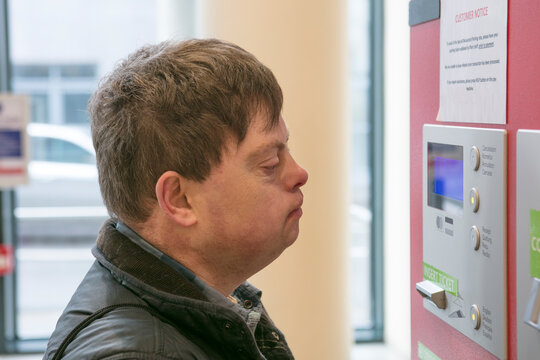 Man with down syndrome at ticket machine in train station, Galway, Ireland