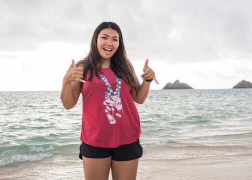 Woman giving thumbs up, Lanikai Beach, Oahu, Hawaii