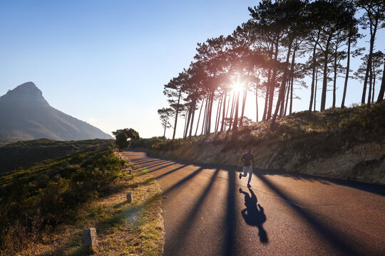 Young male runner running on sunlit rural road, Cape Town, Western Cape, South Africa
