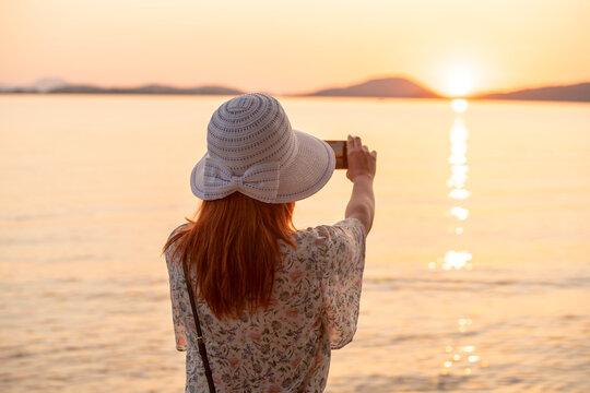 Tourist taking photograph of sunset on beach