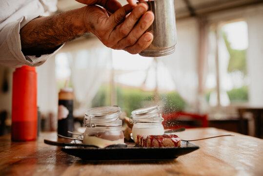 Chef sprinkling icing sugar on dessert
