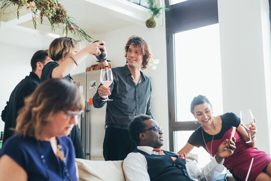 Businessmen and businesswomen celebrating with wine in loft office