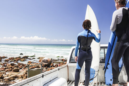 Boy surfer and father standing on back of truck looking out to sea, rear view, Cape Town, Western Cape, South Africa