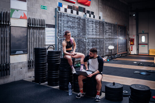 Young woman and man training together in gym, sitting on weights with smartphone and laptop