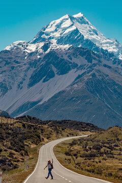 Hiker crossing road leading towards mountains, Wanaka, Taranaki, New Zealand