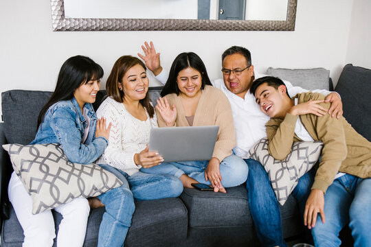 latin family in a video conference on laptop at home in Mexico