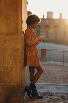 Young woman with afro hair using smartphone, leaning against stone wall, Florence, Toscana, Italy