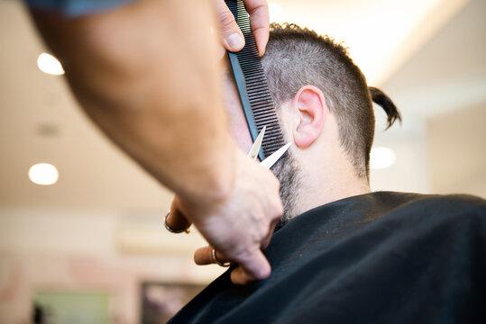 Hairdresser trimming customer's beard in barber shop