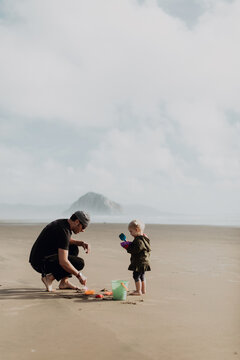 Father and toddler playing with sand on beach, Morro Bay, California, United States