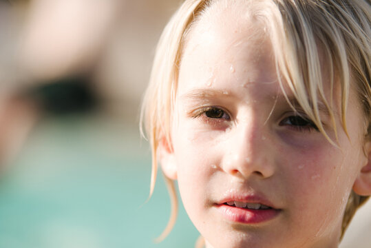 Portrait of boy, swimming pool in background