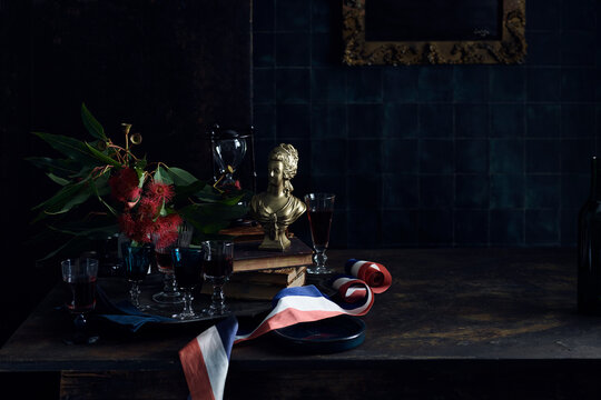 A Bastille Day celebration, tray of glasses with red wine, traditional old master painting and a red white and blue ribbon, colours of the French flag. .