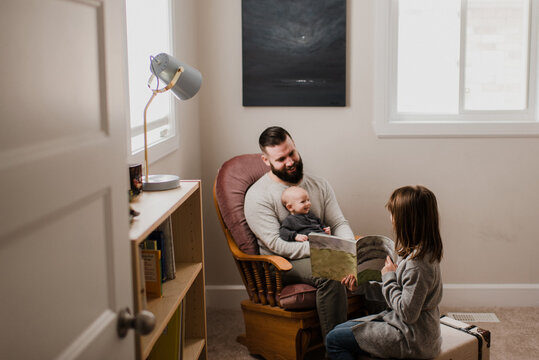 Girl in living room showing book to father and baby brother