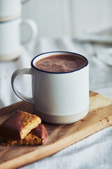 High angle close up of mug of hot chocolate and biscuits.