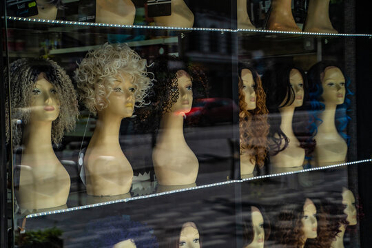 Row of mannequin heads displaying variety of wigs in shop window