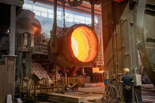 Steelworker inspecting inside of red hot, empty, steel flask in steelworks