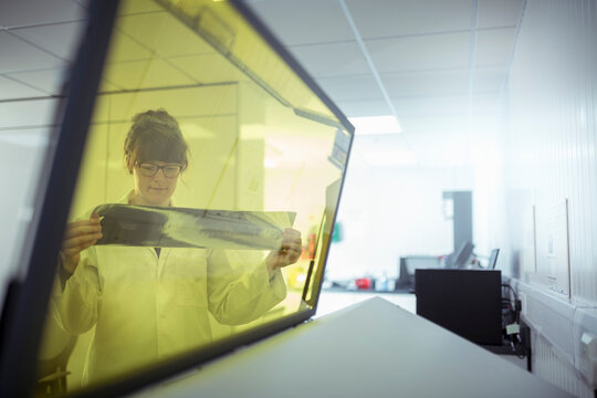 Print scientist examining sample laser etched foil in print factory