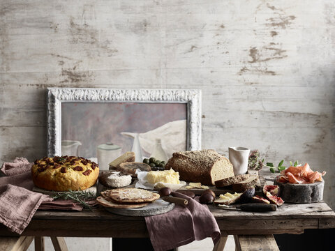 Spread of bread, cheese, figs and ham on table