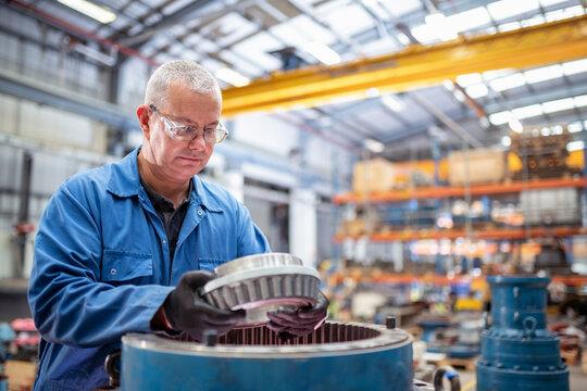 Engineer installing bearings into pump house in electrical engineering factory