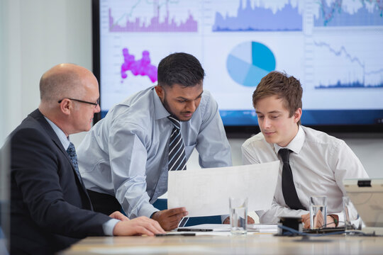 Office workers in meeting with graphs and charts