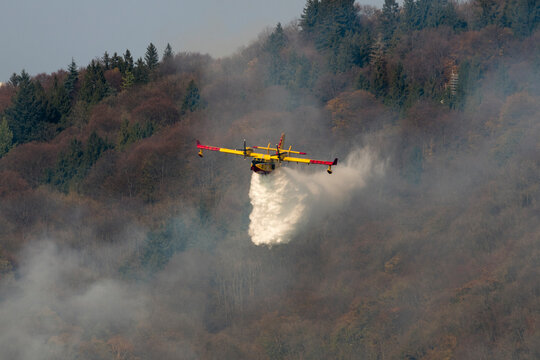 Canadair throwing water to extinguish fire on Sacro Monte, Varese, Italy