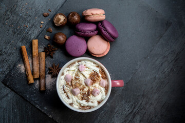 Hot chocolate topped with marshmallows and cream, macaroons, cinnamon sticks, star anise