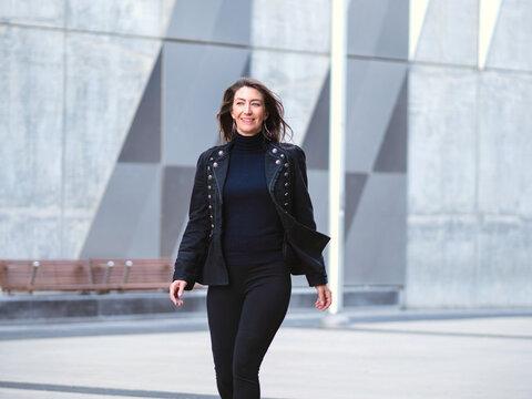 Woman in black walking in city