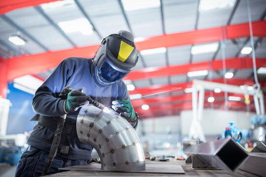 Welder spot welding pipe bend in metal fabrication factory.