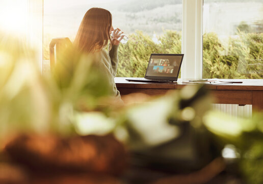 A woman seated at a table at home, taking part in an online meeting, using a laptop.